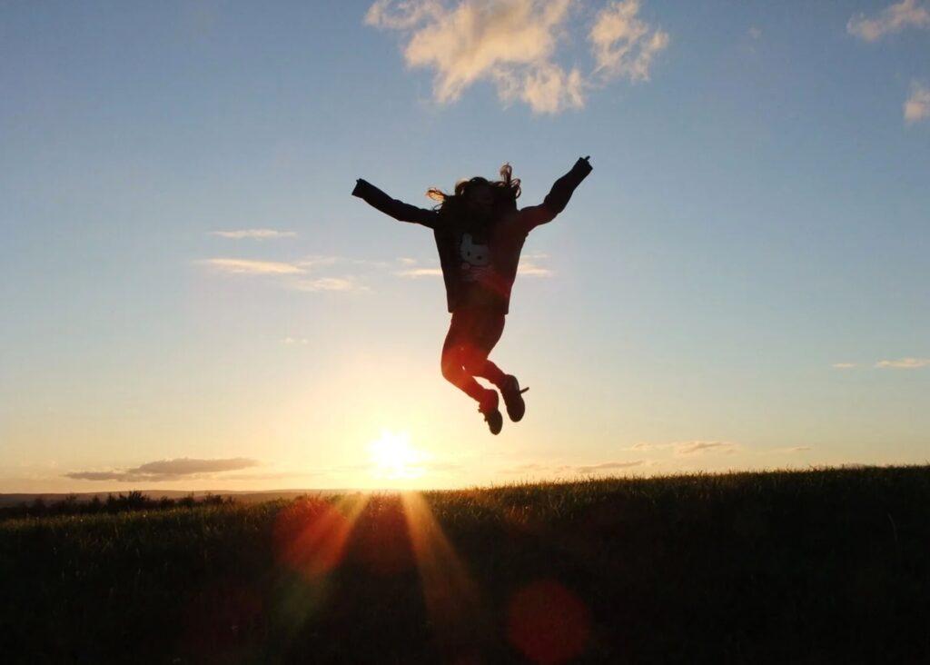 夕日に向かってジャンプする女性