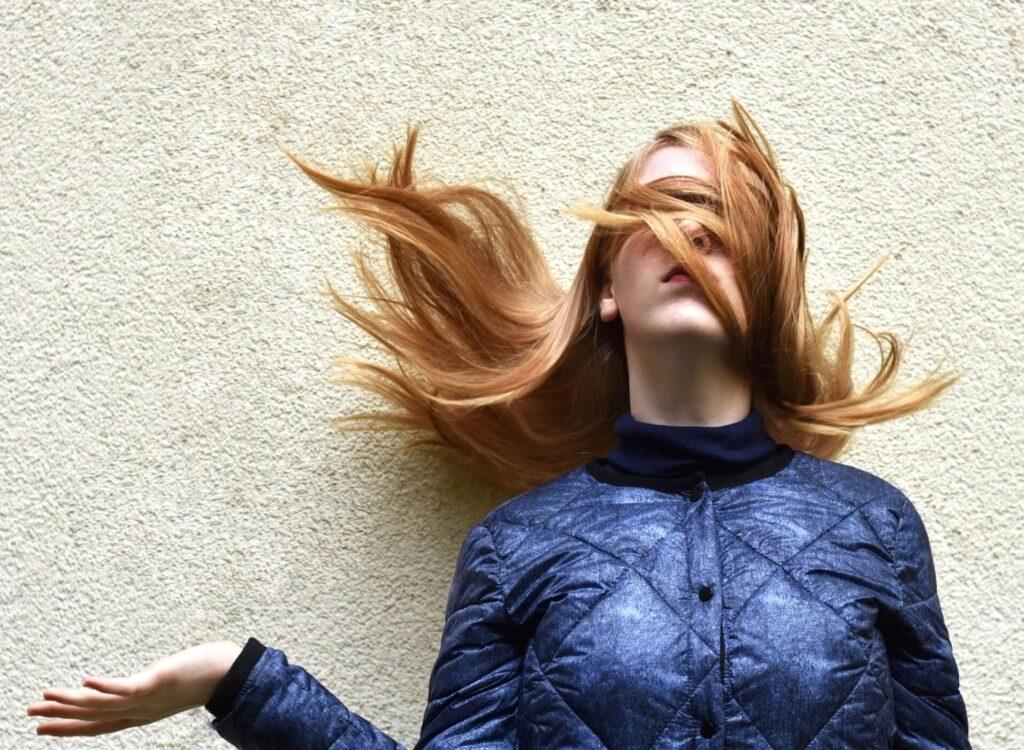 強風で髪の毛がグチャグチャになる女性