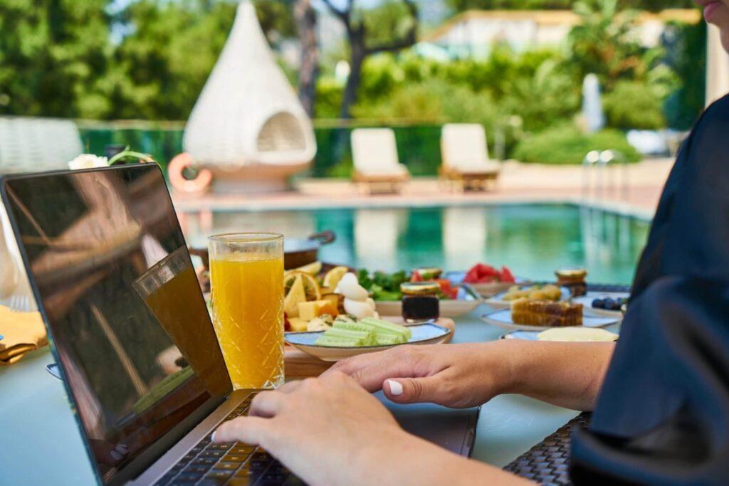 プールサイドでパソコンを触る男性
