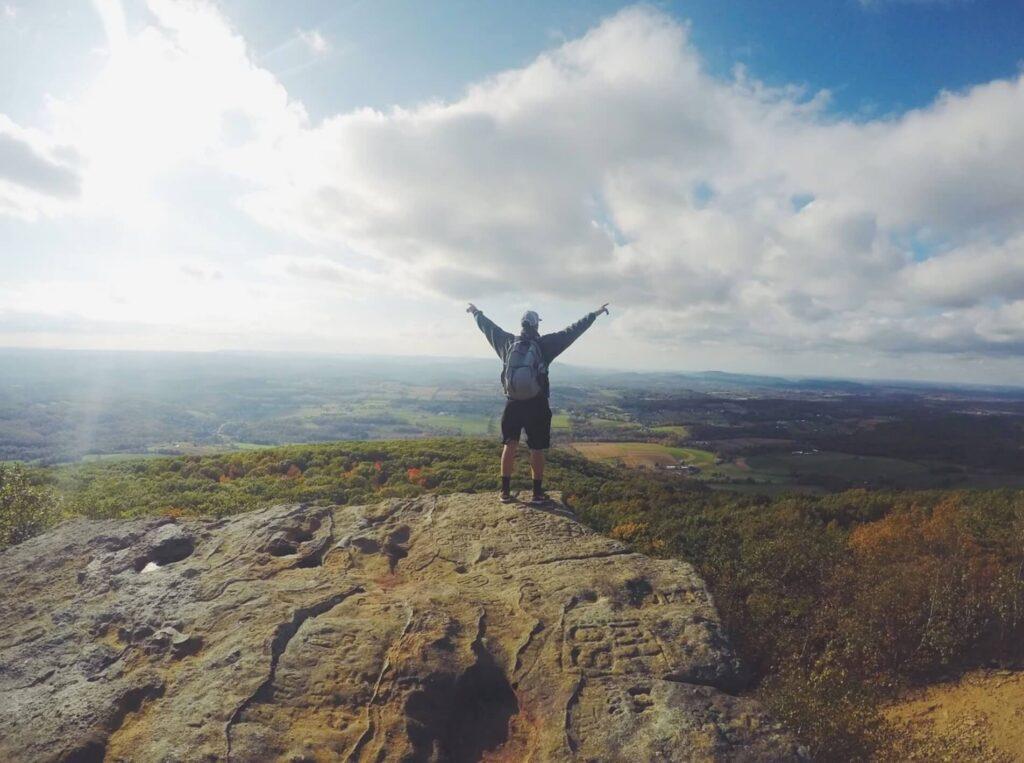山の頂上で喜ぶ男性