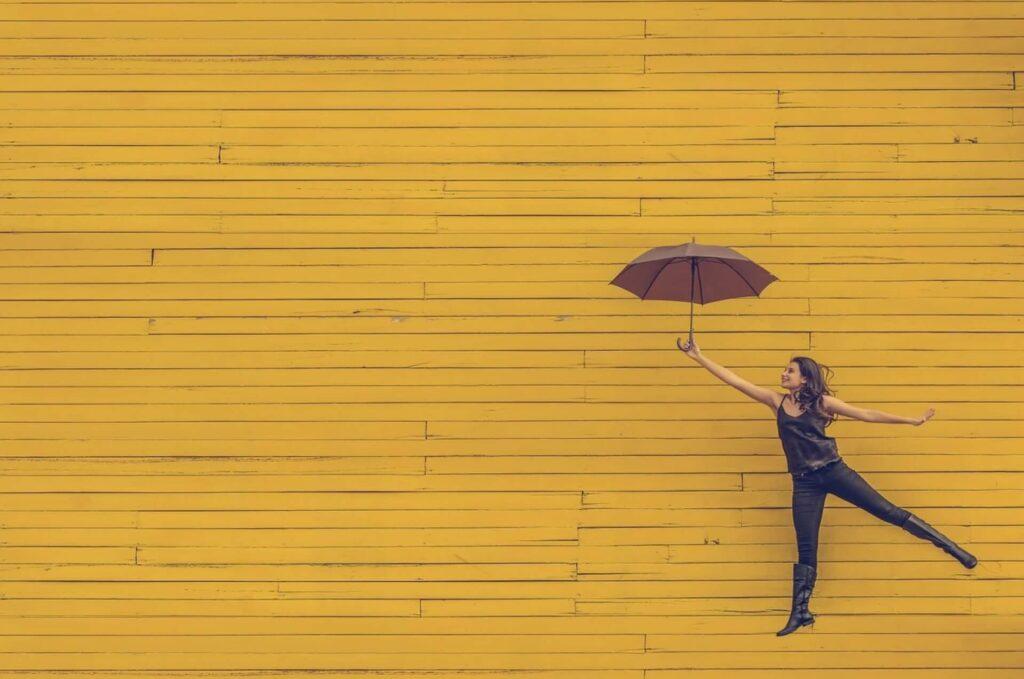 黄色の傘を持って飛び跳ねる女性