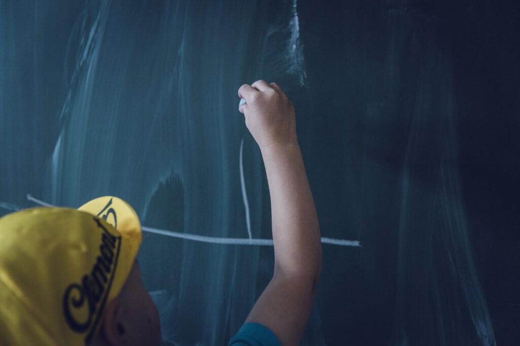 黒板にチョークで書く子供